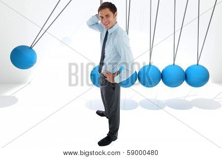 Thinking businessman with hand on head against blue newtons cradle