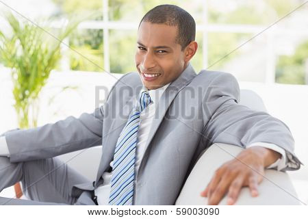 Businessman sitting on couch smiling at camera in the office
