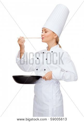 cooking and food concept - smiling female chef with pan and spoon tasting food
