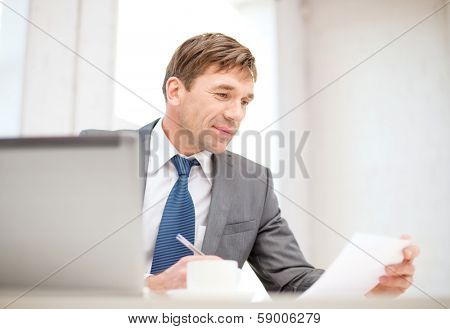 technology, business, internet and office concept - handsome businessman working with laptop computer, coffee and documents