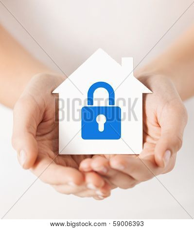 real estate and family home security concept - closeup picture of female hands holding white paper house with blue lock