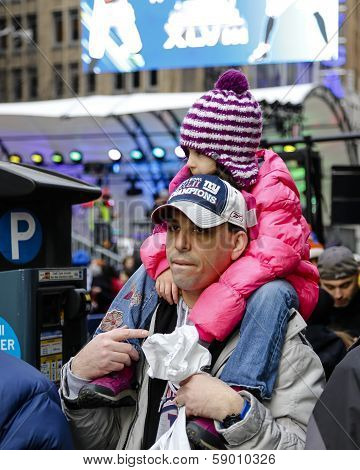 Toddler perched atop her father's shoulders