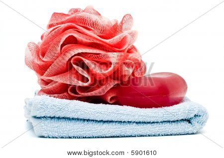 Bath rose and soap bar on top of blue towel
