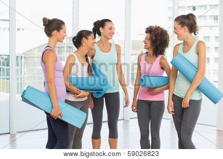 Group of fit smiling young women with exercise mats in a bright exercise room