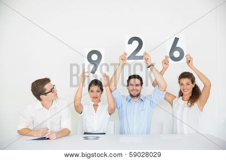 Portrait of business people holding score signs at desk in office