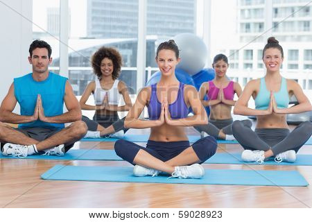 Sporty young people in Namaste position smiling at a bright fitness studio