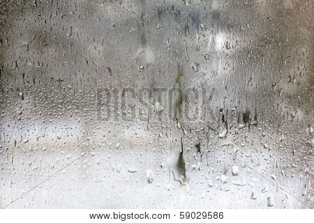 Texture of frozen drops on frosted glass. Abstract winter textured background.