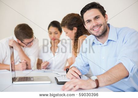Portrait of happy businessman with colleagues discussing in meeting room