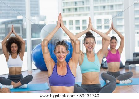 Portrait of smiling sporty young people in Namaste position at a bright fitness studio