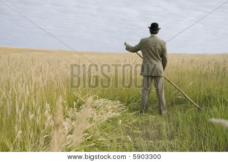 A Man Mows A Grass With A Scythe