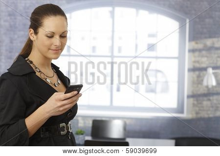 Young businesswoman using mobilephone, writing text message over window.
