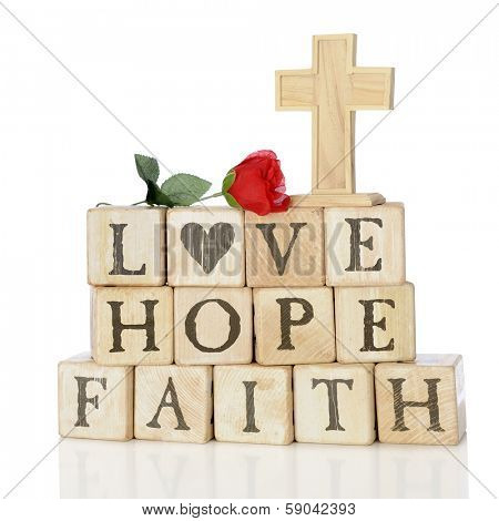 Rustic wood alphabet blocks arranged to say LOVE, HOPE and FAITH.  They're topped with a red rose and a wood cross.  On a white background.