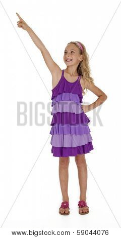 Nine year old girl in purple dress pointing upward on white background.