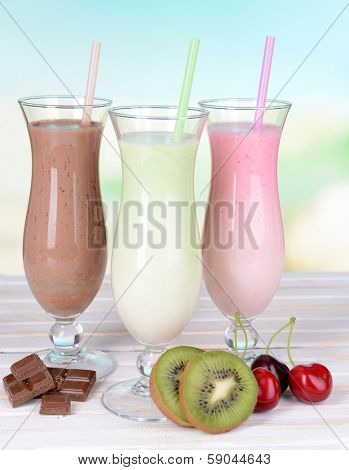 Milk shakes with fruits on table on light blue background