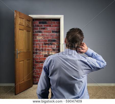 Brick wall blocking the office doorway for a businessman concept for conquering adversity, business obstacle trapped or no way out