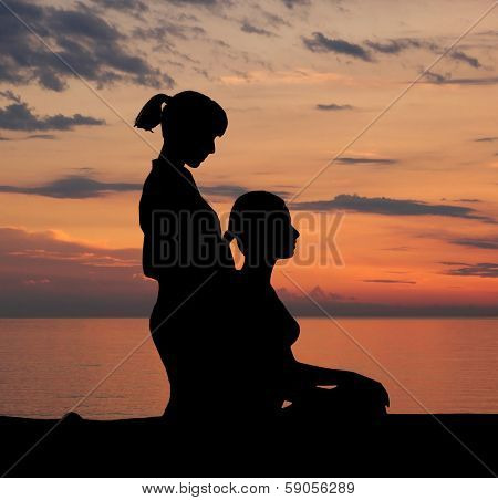 Trace of young woman getting traditional thai stretching massage by therapist isolated on the sunset background