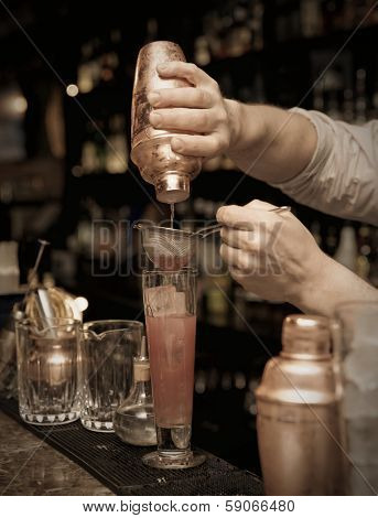 Bartender is straining cocktail in highball glass