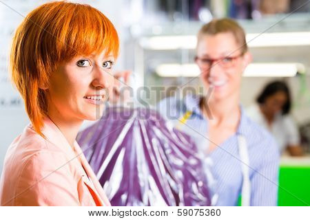 Customer collecting clothes in laundry shop or textile dry-cleaning packed in bag with hanger