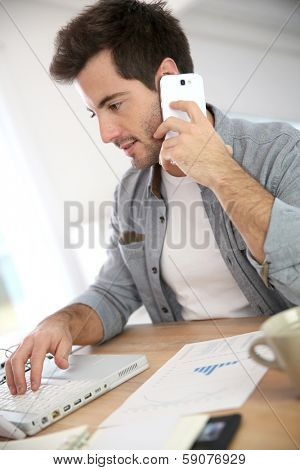 Salesman working from home and talking on phone