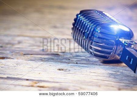 Retro style microphone on old wood table  or stage