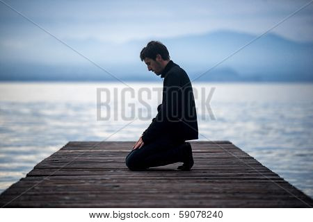 Muslim man praying on an empty dock