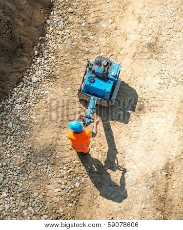 Construction worker working on gravel flattening shot from above