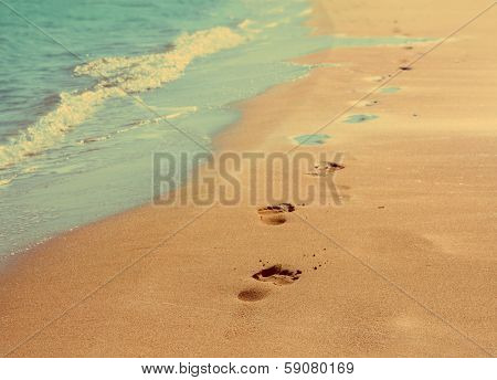 footprints on sand beach along the edge of sea - vintage retro style