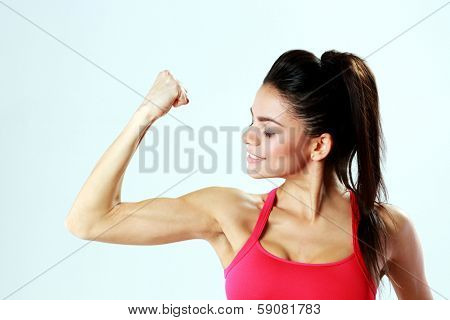 Young sport woman looking at her biceps on gray bakground