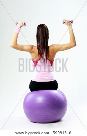 Back view of a young sport woman sitting on fitball with dumbells on gray background