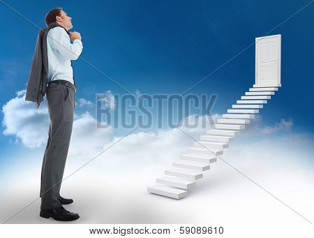 Smiling businessman holding his jacket against steps leading to closed door in the sky