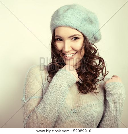Cheerful attractive young girl smiling and looking at camera,  in warm clothes, toned