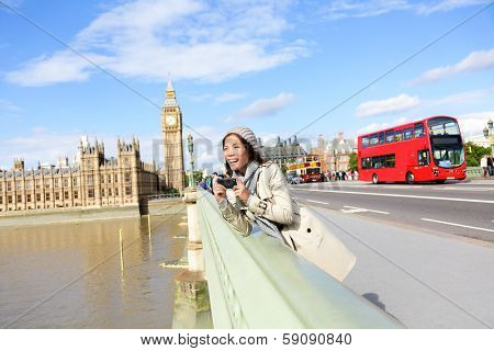 London travel woman tourist by Big Ben and red double decker bus. Girl taking photo on Westminster Bridge with smart phone camera over River Thames, London, England, Great Britain, UK.