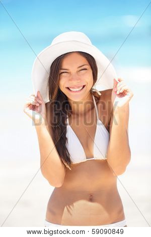Beach woman happy and playful smiling laughing playful and cheerful in summer sun. Beautiful multiracial Asian Chinese / Caucasian woman wearing white beach hat and bikini.