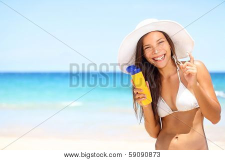 Sunscreen beach woman in bikini applying sun block solar cream for UV protection. Girl smiling to camera, wearing white sun hat, happy on vacation travel holiday. Hawaii, USA