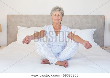 Full length of senior woman meditating in bed at home
