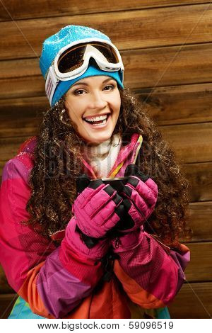 Happy woman in ski wear with cup of a hot drink against wooden wall
