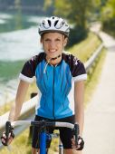 stock photo of young women  - young woman on road bike looking at camera - JPG