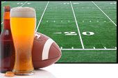 A frothy glass of beer with an American Football in front of a big screen television. Great for Supe
