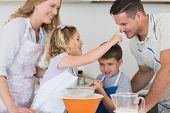 stock photo of flour sifter  - Playful girl touching nose of father while baking cookies with family in kitchen - JPG