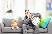 Young man in pajamas holding a big wall clock seated on couch with teddy bear next to him, at home