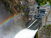 stock photo of dam  - A rainbow is visible above one of the double spillways of Boundary Dam - JPG