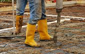 pic of concrete pouring  - Builders pour concrete onto the foundations of a small house - JPG