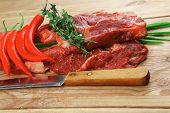 raw meat : boned fresh lamb ribs served with thyme , red chili pepper , and green onion on wooden bo