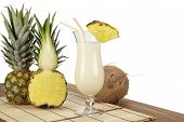 stock photo of pina-colada  - A Pina Colada a half of a pineapple and a coconut are standiing on a tabletop of acacia wood - JPG