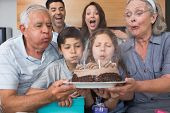 Extended family blowing candles on cake in the living room at home