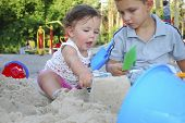 Brother And Sister Playing In The Sand On The Playground.