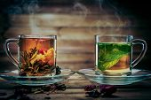 image of pot gold  - Glass cups with tea flower and peppermint tea against wooden background  - JPG