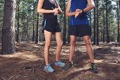 picture of gps  - Trail running couple check time on their gps watch for tracking pace - JPG