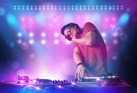 picture of disc jockey  - Young disc jockey mixing music on turntables on stage with lights and stroboscopes - JPG