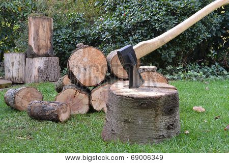 Axe and wooden tree logs